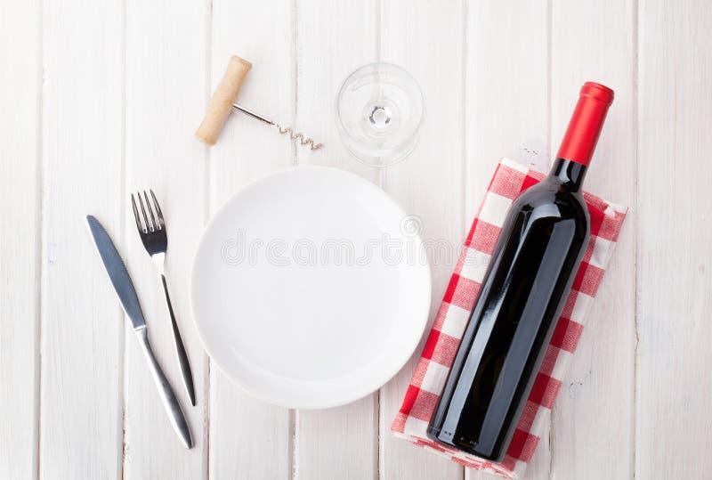 Apresente o ajuste com placa, vidro de vinho e a garrafa de vinho tinto vazios imagens de stock royalty free