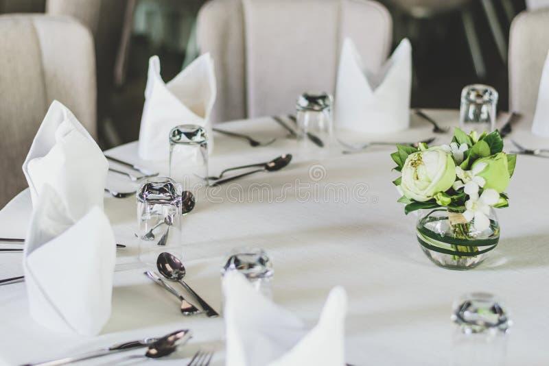 Apresente o ajuste para a sala de jantar, a tabela é decorado com flowe fotos de stock