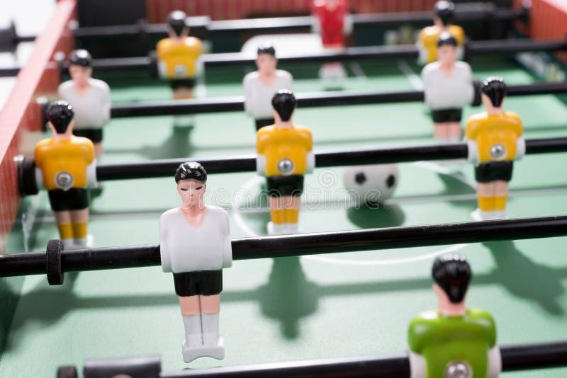 Apresente o jogo de futebol com branco e os jogadores amarelos team no jogo do retrocesso do futebol da tabela foto de stock