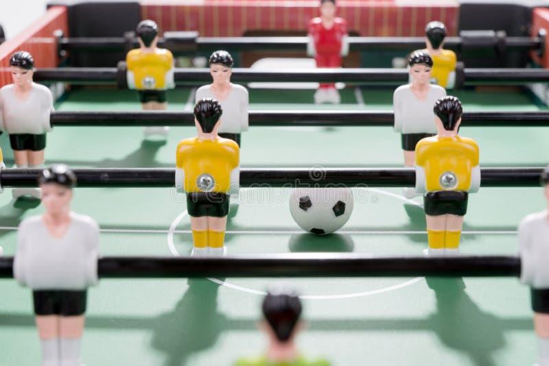 Apresente o jogo de futebol com branco e os jogadores amarelos team no jogo do retrocesso do futebol da tabela imagens de stock royalty free
