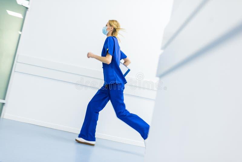 apresse o cirurgião fêmea em máscaras médicas com corredor do diagnóstico fotografia de stock