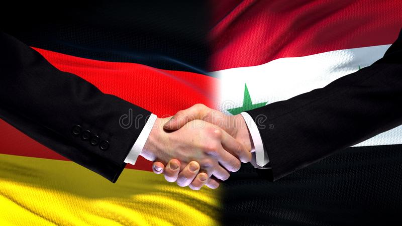 Apretón de manos de Alemania y de Siria, relaciones internacionales de la amistad, fondo de la bandera fotos de archivo