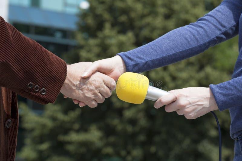 Apretón de manos antes de la entrevista de los medios imagenes de archivo