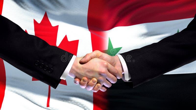 Apretón de manos de Canadá y de Siria, relaciones internacionales de la amistad, fondo de la bandera fotos de archivo