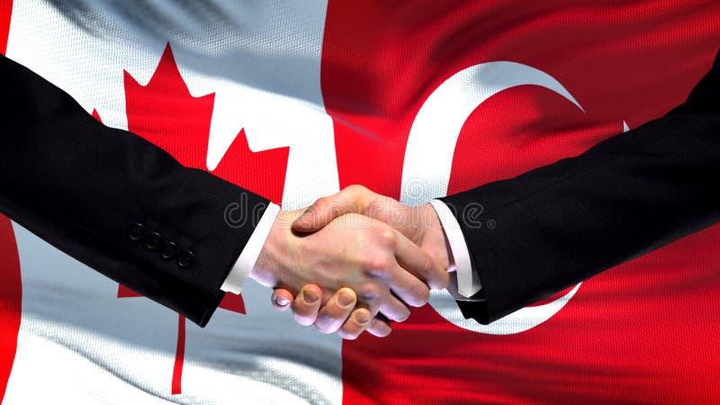 Apretón de manos de Canadá y de Turquía, relaciones internacionales de la amistad, fondo de la bandera foto de archivo libre de regalías