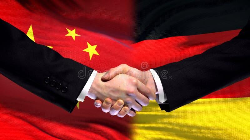 Apretón de manos de China y de Alemania, relaciones internacionales de la amistad, fondo de la bandera imagenes de archivo