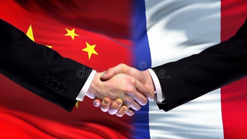 Apretón de manos de China y de Francia, relaciones internacionales de la amistad, fondo de la bandera fotos de archivo