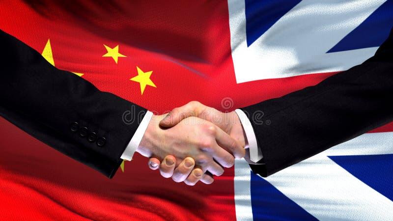 Apretón de manos de China y de Gran Bretaña, amistad internacional, fondo de la bandera imagen de archivo libre de regalías