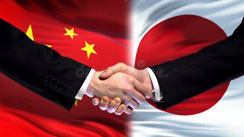 Apretón de manos de China y de Japón, relaciones internacionales de la amistad, fondo de la bandera imagenes de archivo