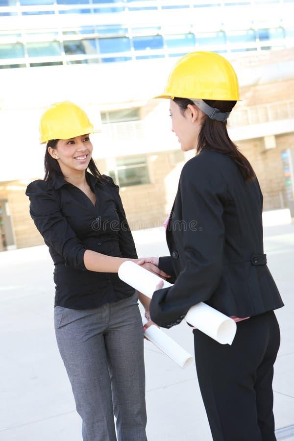 Apretón de manos de las mujeres de la construcción del asunto fotos de archivo