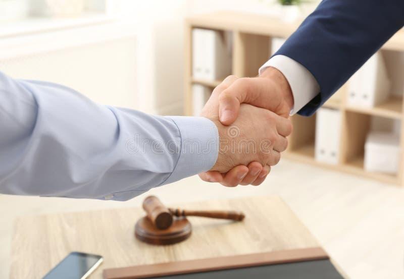 Apretón de manos del abogado con el cliente sobre la tabla en oficina imagenes de archivo