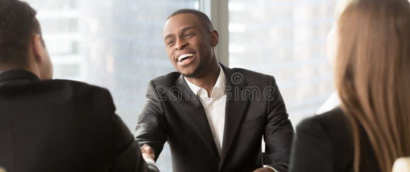 Apretón de manos del encargado de la hora que felicita candidatura negra con entrevista de trabajo acertada foto de archivo libre de regalías