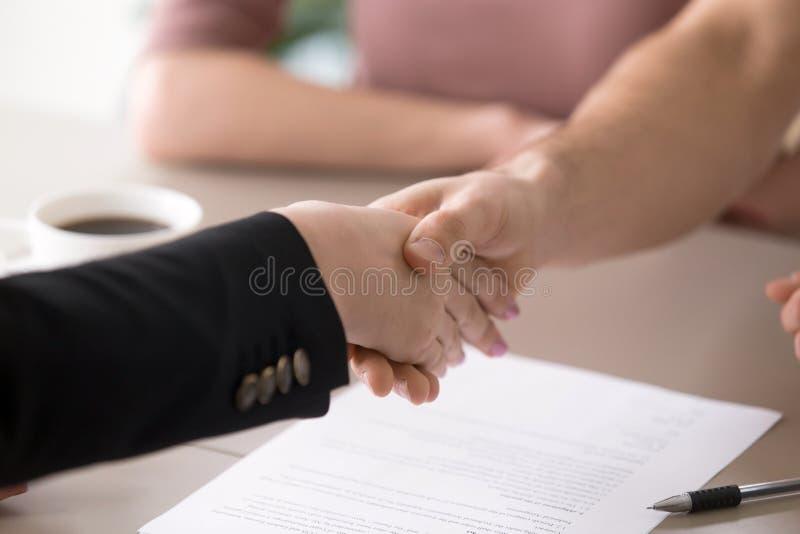 Apretón de manos del hombre y de la mujer después de firmar los documentos, de acertado foto de archivo libre de regalías
