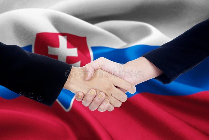 Apretón de manos del negocio con la bandera de Eslovaquia imagen de archivo libre de regalías