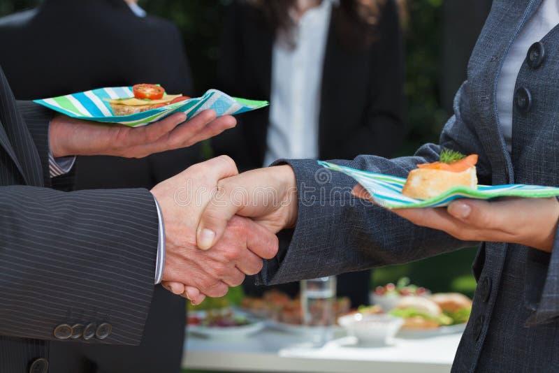 Apretón de manos del negocio durante almuerzo fotos de archivo