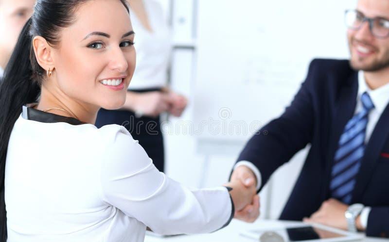 Apretón de manos del negocio en la reunión o la negociación en la oficina Satisfacen a dos socios de los empresarios porque firma imagen de archivo