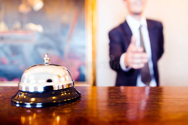Apretón de manos del saludo del recepcionista de la campana de la recepción del hotel foto de archivo libre de regalías