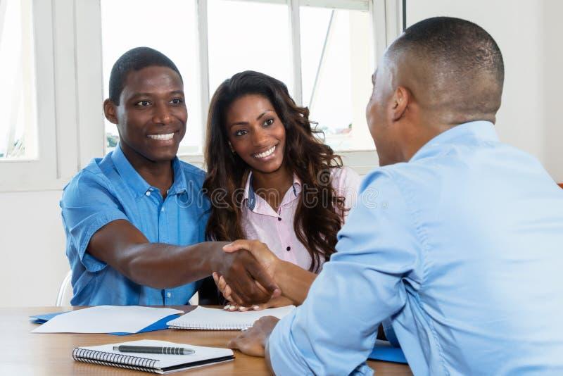 Apretón de manos después de firmar el contrato con el agente inmobiliario fotografía de archivo