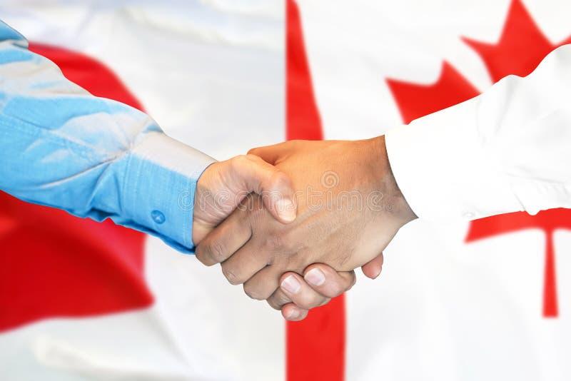 Apretón de manos en fondo de la bandera de Canadá y de Japón fotos de archivo libres de regalías