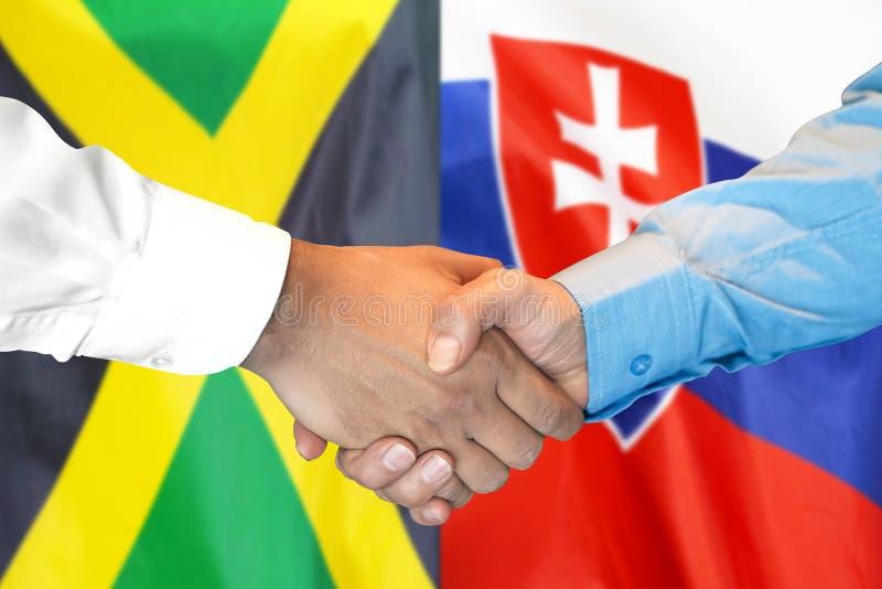 Apretón de manos en fondo de la bandera de Jamaica y de Eslovaquia fotos de archivo libres de regalías