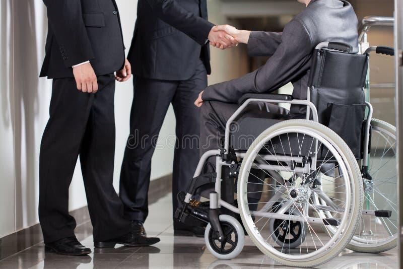 Apretón de manos entre el hombre y el jefe discapacitados fotos de archivo libres de regalías