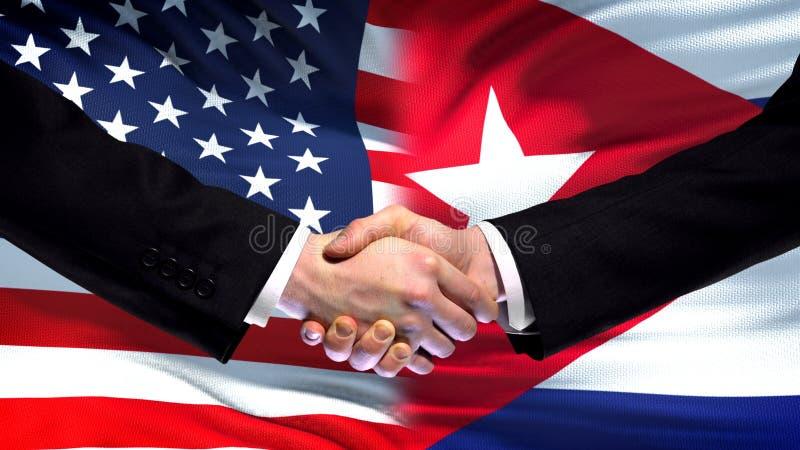 Apretón de manos de Estados Unidos y de Cuba, amistad internacional, fondo de la bandera imagen de archivo libre de regalías