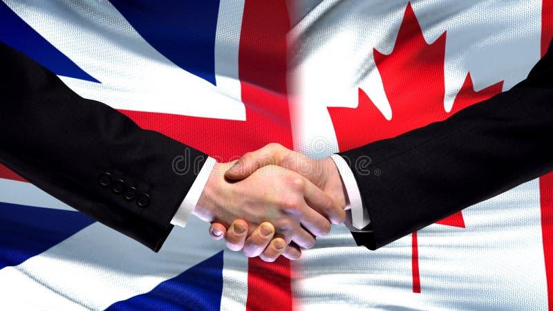 Apretón de manos de Gran Bretaña y de Canadá, amistad internacional, fondo de la bandera foto de archivo libre de regalías