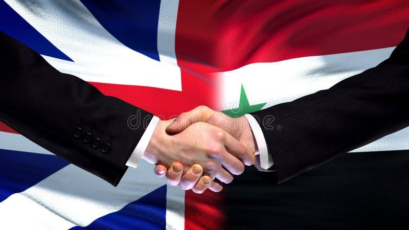 Apretón de manos de Gran Bretaña y de Siria, amistad internacional, fondo de la bandera fotografía de archivo libre de regalías