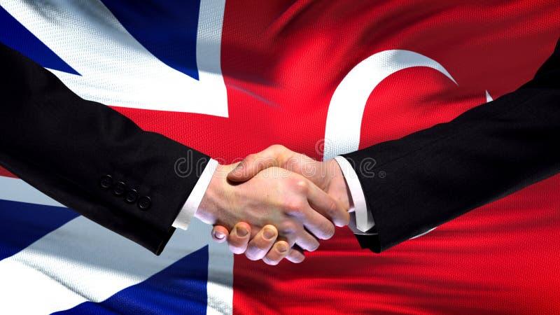 Apretón de manos de Gran Bretaña y de Turquía, amistad internacional, fondo de la bandera imagenes de archivo