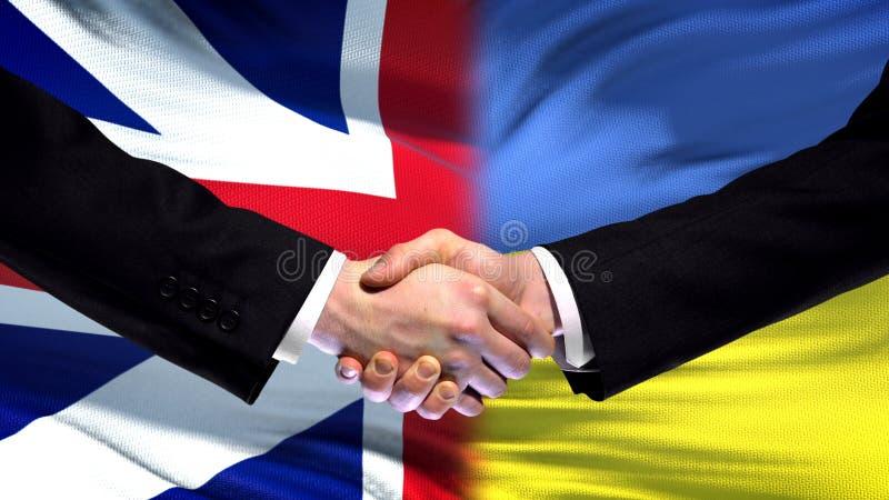 Apretón de manos de Gran Bretaña y de Ucrania, amistad internacional, fondo de la bandera fotos de archivo