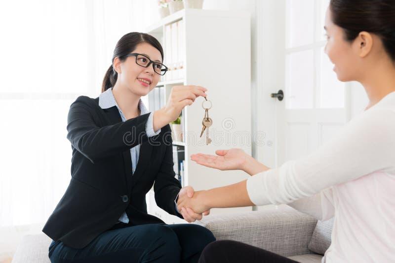 Apretón de manos hermoso de la dependienta con su cliente foto de archivo