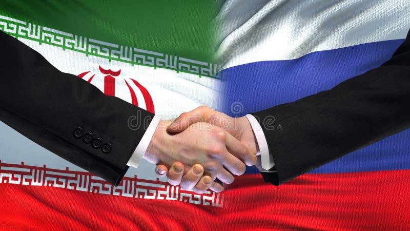 Apretón de manos de Irán y de Rusia, relaciones internacionales de la amistad, fondo de la bandera imagenes de archivo