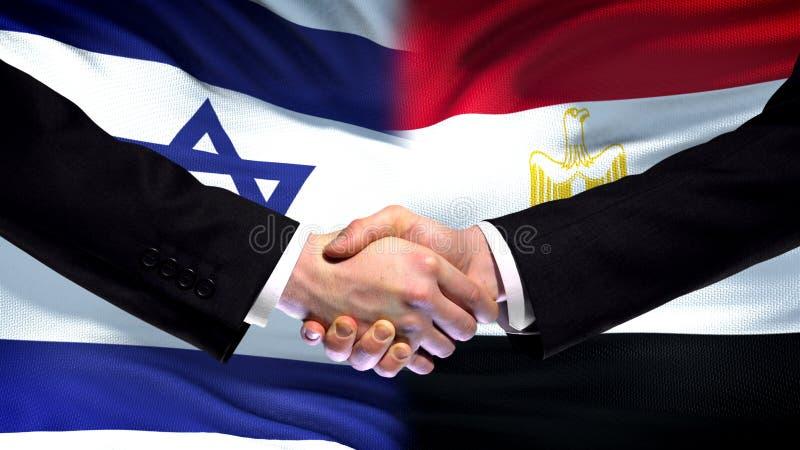 Apretón de manos de Israel y de Egipto, relaciones internacionales de la amistad, fondo de la bandera fotografía de archivo libre de regalías