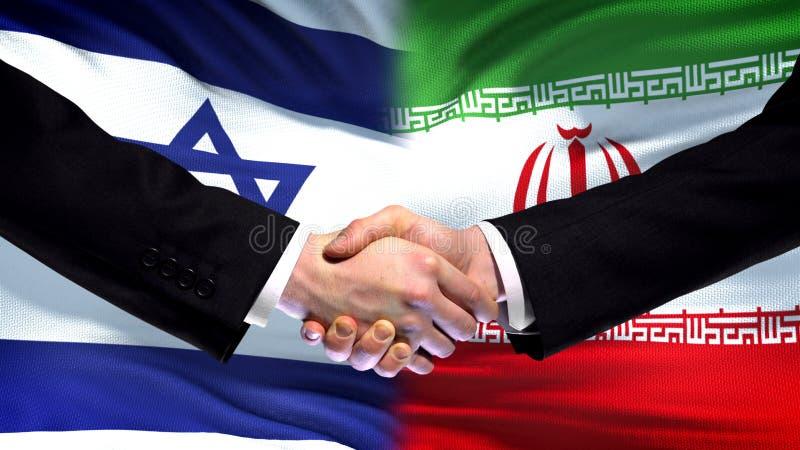 Apretón de manos de Israel y de Irán, relaciones internacionales de la amistad, fondo de la bandera imagen de archivo libre de regalías