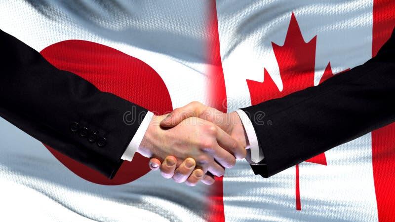 Apretón de manos de Japón y de Canadá, relaciones internacionales de la amistad, fondo de la bandera imagen de archivo libre de regalías