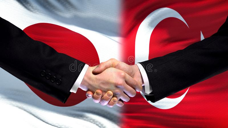 Apretón de manos de Japón y de Turquía, relaciones internacionales de la amistad, fondo de la bandera fotografía de archivo libre de regalías
