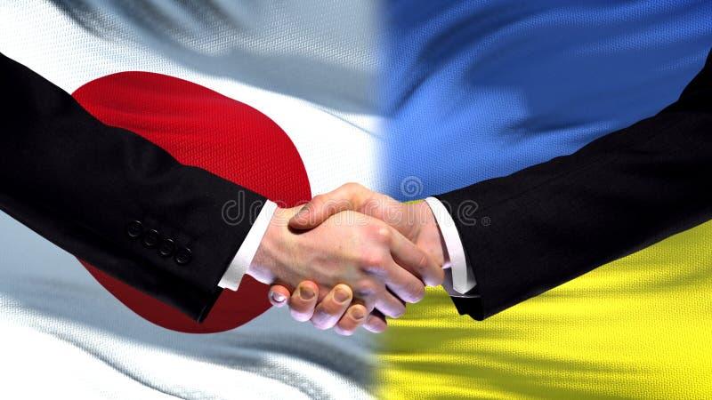 Apretón de manos de Japón y de Ucrania, relaciones internacionales de la amistad, fondo de la bandera fotografía de archivo libre de regalías