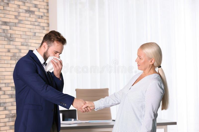 Apretón de manos maduro de la mujer con el hombre joven enfermo fotos de archivo libres de regalías