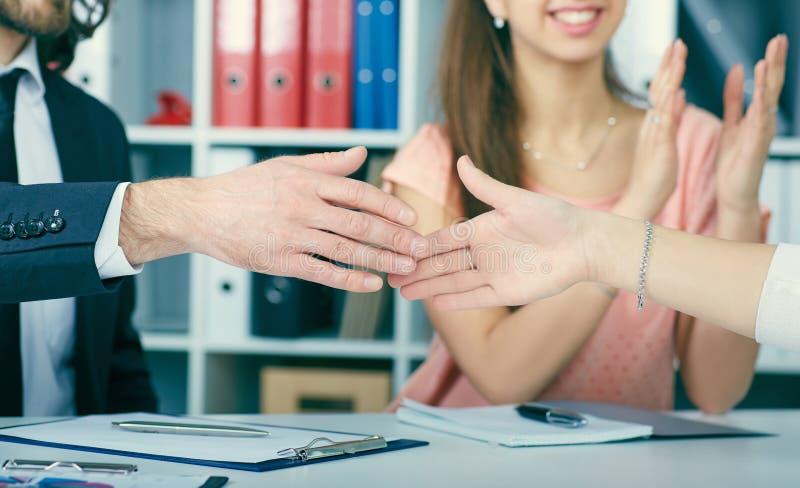 Apretón de manos masculino y femenino en oficina imagenes de archivo