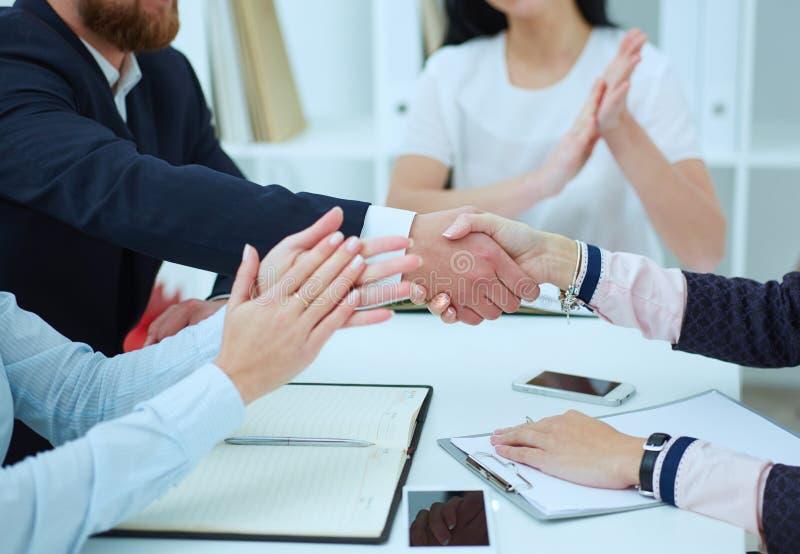 Apretón de manos masculino y femenino en oficina Concepto serio del negocio y de la sociedad Apenas entrega la tabla Socios hecho imagen de archivo