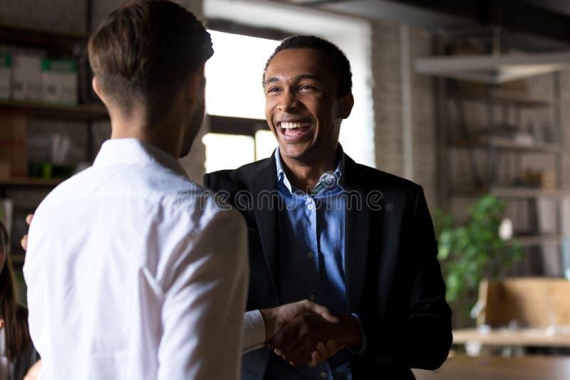 Apretón de manos negro feliz del CEO que recompensa al trabajador acertado, employe imagen de archivo libre de regalías