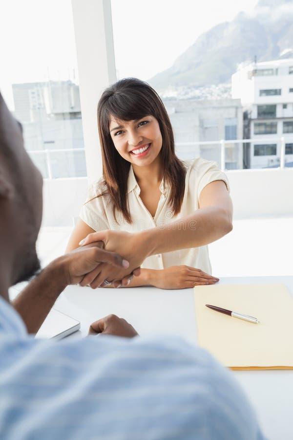 Apretón de manos para sellar un trato después de una reunión de negocios imagenes de archivo