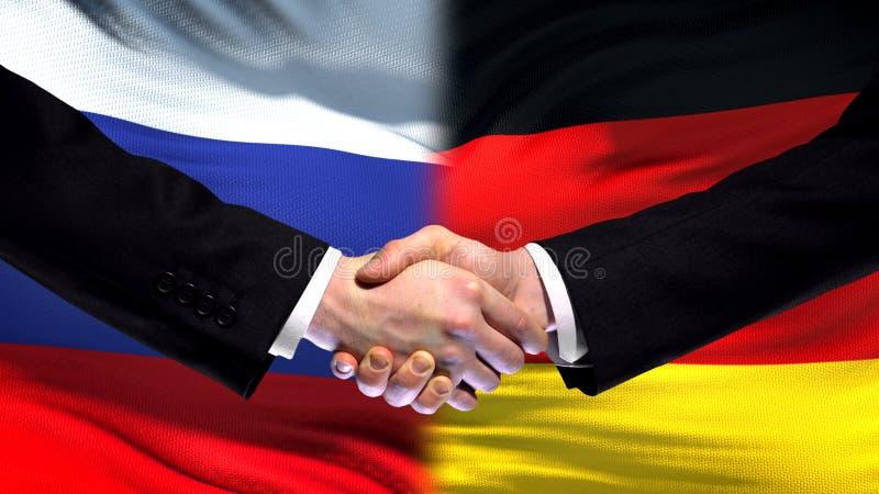 Apretón de manos de Rusia y de Alemania, cumbre internacional de la amistad, fondo de la bandera imagen de archivo libre de regalías