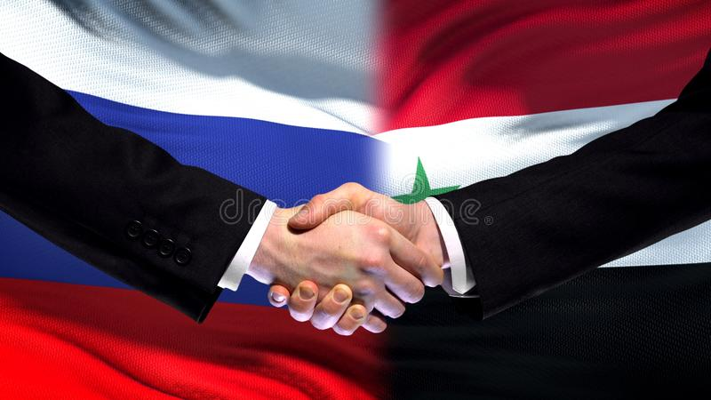 Apretón de manos de Rusia y de Siria, relaciones internacionales de la amistad, fondo de la bandera imagen de archivo
