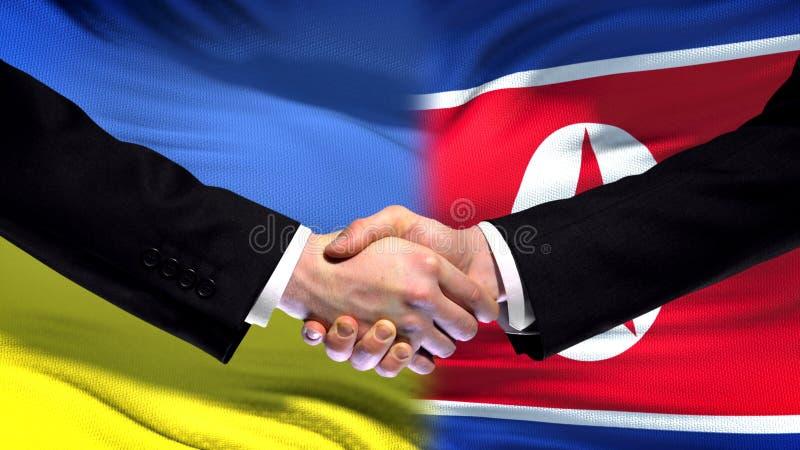 Apretón de manos de Ucrania y de Corea del Norte, amistad internacional, fondo de la bandera imagenes de archivo