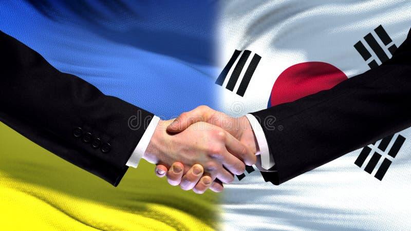 Apretón de manos de Ucrania y de la Corea del Sur, amistad internacional, fondo de la bandera imagenes de archivo