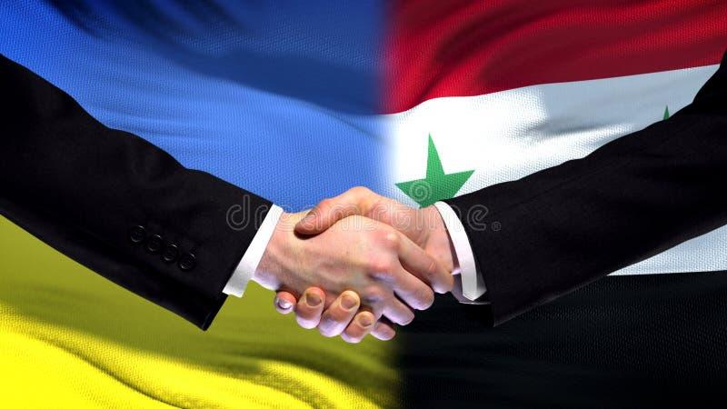 Apretón de manos de Ucrania y de Siria, relaciones internacionales de la amistad, fondo de la bandera imagenes de archivo