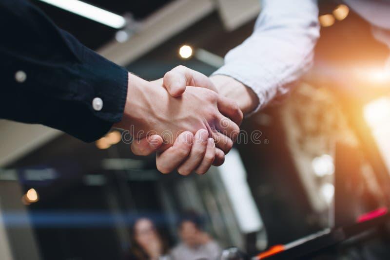 Apretones de manos de los socios comerciales en espacio abierto moderno en el fondo del equipo coworking en nuevo proyecto de ini