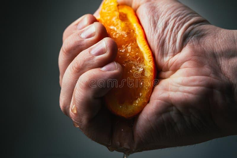 Apretones dramáticos del hombre anaranjados Conceptis cansó de trabajo foto de archivo