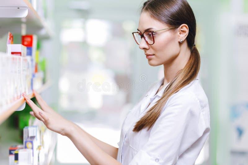Apretty tar den slanka flickan med mörkt hår och exponeringsglas som bär en medicinsk overall, något från hyllan i ett nytt apote arkivfoton